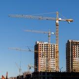 Konstruktionskranar och byggda hus på bakgrund för blå himmel arkivfoto