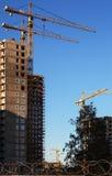 Konstruktionskranar och byggda hus på bakgrund för blå himmel royaltyfri foto