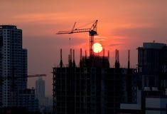 Konstruktionskranar och byggnadssilhouettes över sunen på soluppgången. Royaltyfri Bild