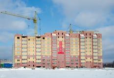 Konstruktionskranar och hus under konstruktion Arkivfoton