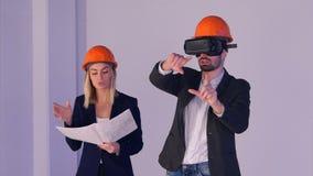 Konstruktionsman- och kvinnligteknikerer i hjälmar med VR rullar med ögonen klara av byggnadsprojekt i 3d Royaltyfria Bilder