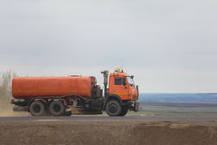 Konstruktionsmaskineri - bevattna lastbilen på huvudvägen bland fält Fotografering för Bildbyråer