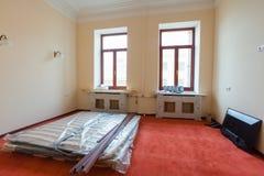 Konstruktionsmaterial, möblemang, TV och telefonen är på golvet av lägenheten i hotellet under under-renovering Royaltyfri Bild