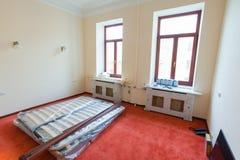 Konstruktionsmaterial, möblemang, TV och telefonen är på golvet i lägenheten av hotellet under under-renovering, Royaltyfri Bild