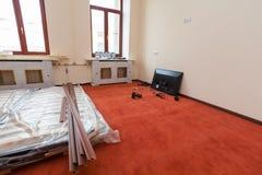 Konstruktionsmaterial, möblemang, TV och telefonen är på golvet i lägenheten av hotellet under under-renovering Arkivfoto