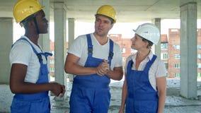 Konstruktionsmedarbetare som diskuterar om plats för konstruktion för arbetsplan arkivfilmer