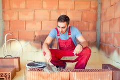 Konstruktionsmurare, industriarbetare med hjälpmedel som bygger väggar Arkivfoto