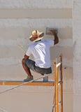 Konstruktionsmurare som renoverar fasaden av ett hus Arkivfoto