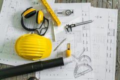 Konstruktionsplan med hjälm- och teckningshjälpmedel på ritningar Arkivbild