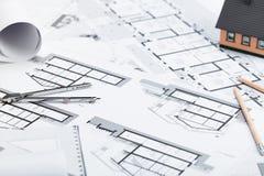 Konstruktionsplan med teckningshjälpmedel och husminiatyren på blått royaltyfri fotografi