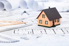 Konstruktionsplan med teckningshjälpmedel och husminiatyren på blått arkivbilder