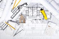 Konstruktionsplan med teckningshjälpmedel och husminiatyren på blått royaltyfria foton