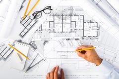 Konstruktionsplan och manhänder som drar på ritningar Royaltyfri Foto