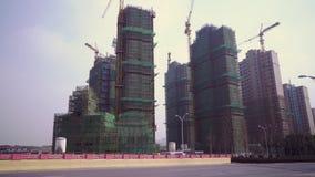 Konstruktionsplats av en typisk utveckling med skogar och kranar i den bostads- fjärdedelen av Shanghai, Kina arkivfilmer