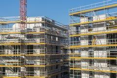 Konstruktionsplats av ett nytt hus med materialet till byggnadsställning på fasaden Royaltyfri Foto