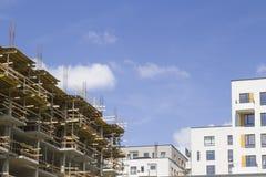 Konstruktionsplats av nya hus med kranar mot bakgrund för blå himmel Royaltyfri Foto