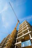Konstruktionsplats med byggnad med kranen och blå himmel Arkivbilder