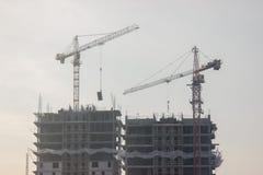 Konstruktionsplats med den gula kranen på bakgrund för blå himmel Konstruktion byggnation, att lyfta som är tungt, laddar upp royaltyfri foto