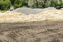 Konstruktionsplats med högar av sand, grus och jord och spår royaltyfria bilder