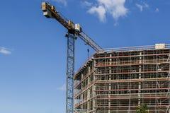 Konstruktionsplats med kranar på bakgrund för blå himmel Nybygget och materialet till byggnadsställning Royaltyfri Fotografi