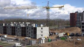 Konstruktionsplats med kranen och arbetare som framlänges bygger huset 4K arkivfilmer