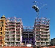 Konstruktionsplats med materialet till byggnadsställning och kranen Royaltyfria Bilder