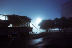 Konstruktionsplats på stadsgatan som täckas med dimma, nattetid, b Royaltyfri Fotografi