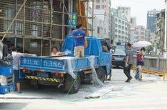 Konstruktionsplatsen, arbetare är ladda och lasta av byggnadsmaterial Royaltyfri Fotografi