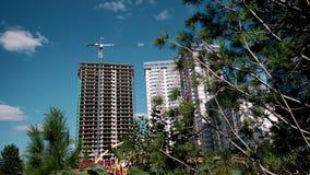 Konstruktionsprocess av skyskrapan och nya lägenheter med kranar på en blå himmel Nytt hus i ett nytt bostads- komplex lager videofilmer