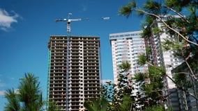 Konstruktionsprocess av skyskrapan och nya lägenheter med kranar på en blå himmel Nytt hus i ett nytt bostads- komplex stock video