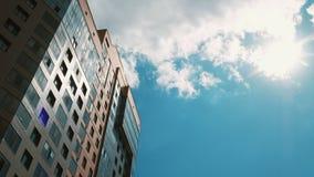 Konstruktionsprocess av skyskrapan och nya lägenheter på en blå himmel Nytt hus i ett nytt bostads- komplex lager videofilmer
