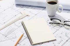 Konstruktionsprojekt planläggning Öppna ritningar med en blyertspenna a Arkivfoto