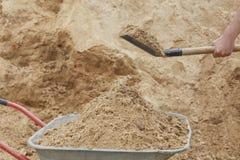 Konstruktionsskottkärra som fylls med sand en skyffel royaltyfri bild