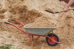 Konstruktionsskottkärra som fylls med sand en skyffel royaltyfri foto