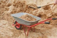 Konstruktionsskottkärra som fylls med sand en skyffel arkivfoton
