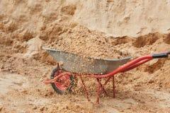Konstruktionsskottkärra som fylls med sand en skyffel arkivbild