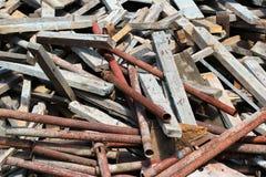 Konstruktionsskräp - gamla träplankor, stänger och rostiga metallrör Arkivfoto