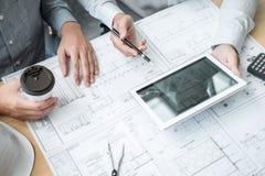 Konstruktionsteknik eller arkitekt som diskuterar en ritning och bygger modellen, medan kontrollera information på att skissa möt royaltyfria foton