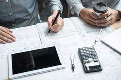 Konstruktionsteknik eller arkitekt som diskuterar en ritning och bygger modellen, medan kontrollera information på att skissa möt royaltyfri bild