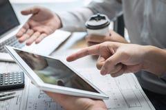 Konstruktionsteknik eller arkitekt som diskuterar en ritning och bygger modellen, medan kontrollera information på att skissa möt arkivfoto