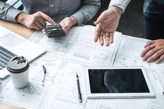 Konstruktionsteknik eller arkitekt som diskuterar en ritning och bygger modellen, medan kontrollera information p? att skissa m?t royaltyfria foton