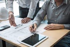 Konstruktionsteknik eller arkitekt som diskuterar en ritning och bygger modellen, medan kontrollera information p? att skissa m?t arkivfoto