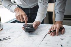 Konstruktionsteknik eller arkitekt som diskuterar en ritning och bygger modellen, medan kontrollera information p? att skissa m?t royaltyfria bilder