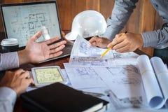 Konstruktionsteknik eller arkitekt som diskuterar en ritning och bygger modellen, medan kontrollera information p? att skissa m?t arkivbild