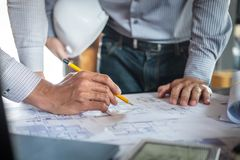 Konstruktionsteknik eller arkitekt som diskuterar en ritning och bygger modellen, medan kontrollera information p? att skissa m?t royaltyfri bild