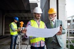 Konstruktionstekniker med ordförandearbetaren som kontrollerar konstruktionsplatsen arkivfoto