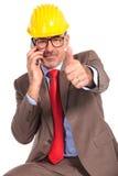 Konstruktionsteknikern som talar på telefonen och, gör det ok tecknet Fotografering för Bildbyråer