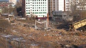 Konstruktionsutrustning är förlovad i rivningen av väggarna av den gamla fabriken arkivfilmer