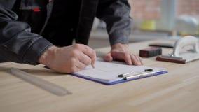 Konstruktor rysuje projekt na prześcieradle papier używać ołówek, zakończenie ręki na stole zbiory
