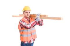 Konstruktor z żółtymi hełma przewożenia drewnami zdjęcie stock